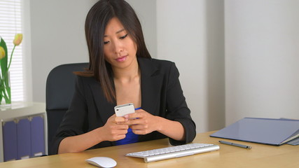 Chinese businesswoman texting at desk