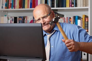 Senior schlägt voller Wut auf seinen Laptop