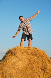 Young happy man on haystack