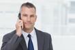 Businessman looking at camera while having a phone call