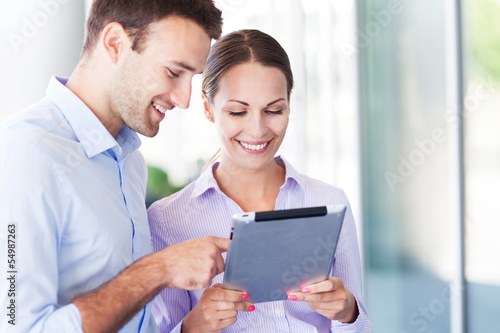 Business people using digital tablet together