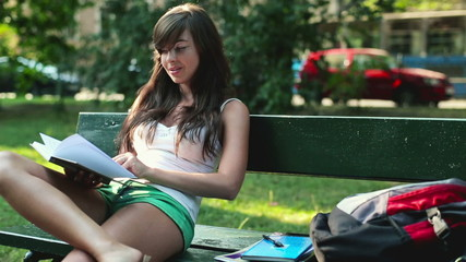 Cute female student reading book in city park