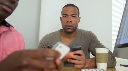 Black businessmen texting on their smartphones