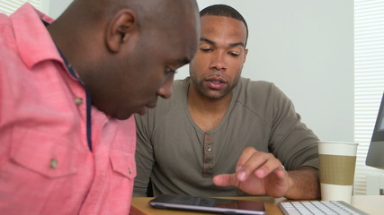 Two black businessmen using a tablet