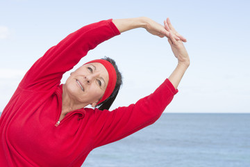 Middle aged woman stretching exercise ocean