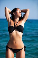 Schöne Frau im Bikini streckt sich