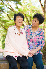 crying Asian senior mother with her senior daughter at outdoor p