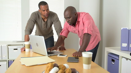 Two Black businessmen working at desk
