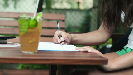 Young female student writing in notebook in cafe