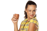 smiling brunette holding her coffee from the machine and winks