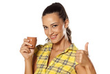 brunette holding her coffee from the machine and shows thumb up