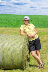 Farmer standing next to hay