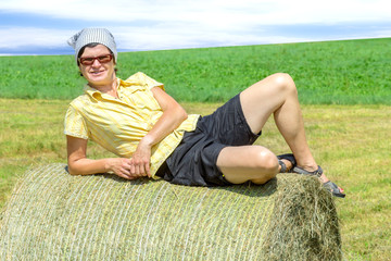 Peasant woman is lying on the hay bales