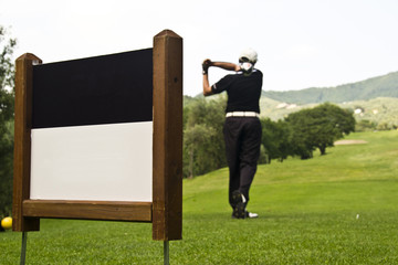 Male golfer swing with a blank sign