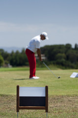 Male golfer focusing on his swing with a blank sign