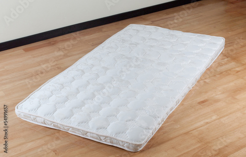 A thin mattress on wooden floor