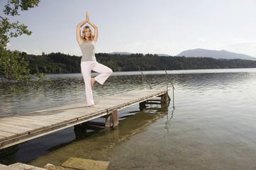 Frau macht Yoga am Steg