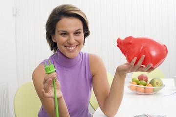 Frau mit grünem Stecker und Sparschwein