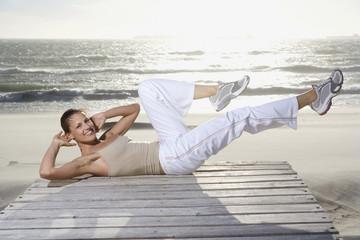 Junge Frau macht Sit-Ups am Strand