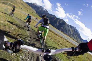Italien, Livigno, Ansicht von Frau und Mann auf dem Mountainbike bergab