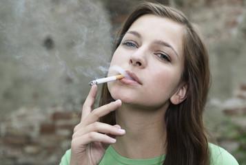 Deutschland, Berlin, Nahaufnahme der jungen Frau, rauchend