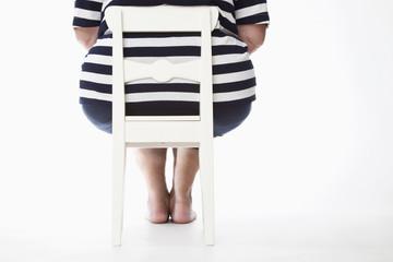 Übergewichtige Frau auf Stuhl, Rückansicht