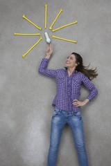 Frau zeigt auf elektrische Glühbirne und lächelt