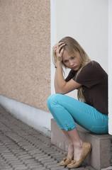 Österreich, Teenager-Mädchen mit dem Kopf in der Hand sitzt an der Haustür