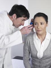Deutschland, Hamburg, Arzt untersucht Ohr des Patienten