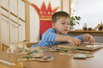 Deutschland, Junge im Kindergarten macht Puzzle