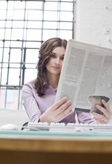 Junge Unternehmerin im Büro liest Zeitung