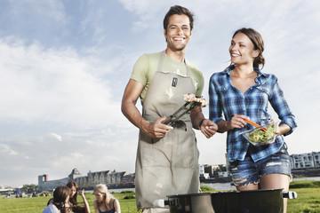 Deutschland, Köln, Mann und Frau, Grillen mit Freunden im Hintergrund