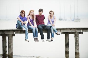 Deutschland, Bayern, Ammersee, Vier Freunde sitzen auf Steg