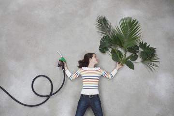 Frau hält Tankstutzen und Pflanze