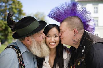 Deutschland, Bayern, Oberbayern, Zwei Männer küssen asiatische Frau auf die Wange