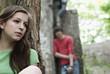 Deutschland, Berlin, junge Frau an Baum gelehnt mit Mann im Hintergrund