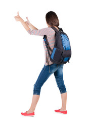 Back view of brunette woman with backpack thumbs up. .