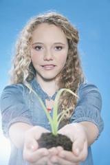 Mädchen, die eine Pflanze hält