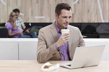 Deutschland, Köln, Geschäftsmann im Café mit Laptop