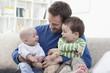 Deutschland, Bayern, München, Vater mit seinen Kindern auf dem Sofa