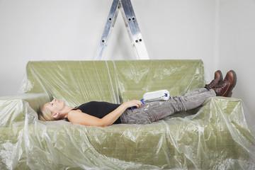 Deutschland, Köln, erwachsene Frau, die während Renovierung auf Sofa ausruht