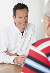 Deutschland, München, Arzt im Gespräch mit Patienten