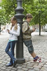 Deutschland, Berlin, Junge und Mädchen stützte sich auf Poller mit Handy