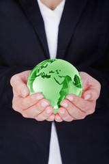 Frau hält grünen Globus