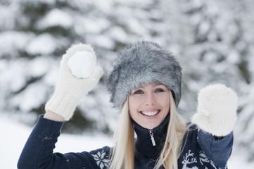 Österreich, Salzburger Land, Altenmarkt, Zauchensee, Junge Frau wirft Schneeball, Lächeln
