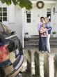 Familie mit Baby stehend vor dem Haus