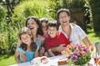 Deutschland, Bayern, Familie mit Kaffee und Kuchen im Garten