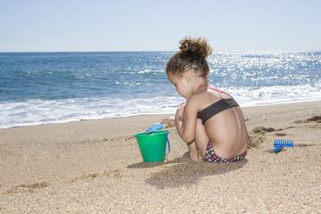 Frankreich, Korsika, Mädchen spielen mit Sand am Strand