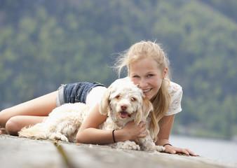 Österreich, Teenager-Mädchen mit Hund auf Anlegestelle, Lächeln