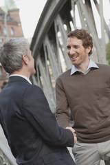 Deutschland, Hamburg, Zwei Geschäftsleute Händeschütteln, Lächeln